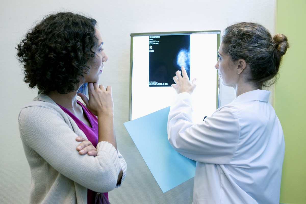 young female doctor pointing to x-ray with patient